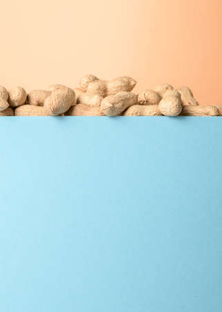 Raw peanuts on a blue-orange background. Conceptual minimalism. 免版税图像