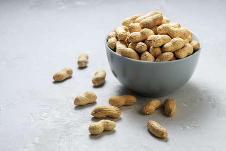 Untreated peanuts in a gray bowl on a concrete background with copies space.