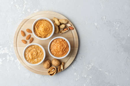 Walnut butter made of peanuts, almonds and walnut on a gray background.