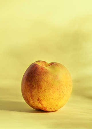 Ripe nectarine on a yellow background with shadows.