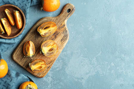 Juicy persimmon slices on a wooden chopping board with copies of space.