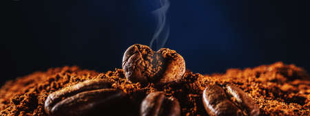 Coffee bean in the form of heart with aromatic smoke from copies of space.