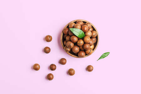 Bowl with macadamia nuts on a pink background with copies of space. Top view.