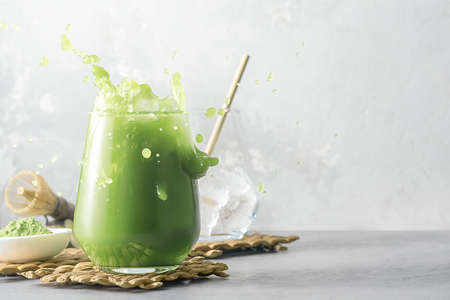 Refreshing matcha tea with ice and splashes on a gray background with copy space.