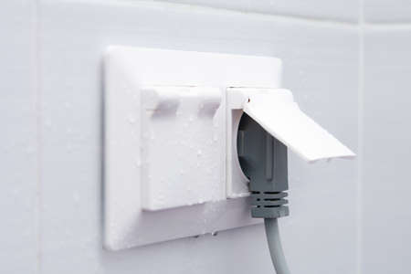 Weatherproof socket on a white tiled wall with water droplets.