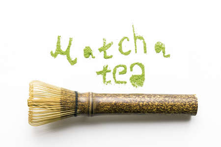 Tea match lettering with a whisk on a white background. Top veiw.