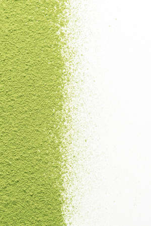 Scattered matcha tea powder on white background with copy space