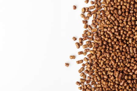 Scattered buckwheat tea pellets on white background with copy space.