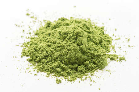 A heap of green matcha tea powder on a white insulated background.