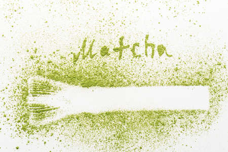 Matcha tea powder with a silhouette of a whisk on a white background.