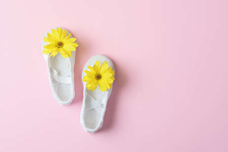 White ballet flats with yellow flowers on a pink background with copy space. Stock Photo