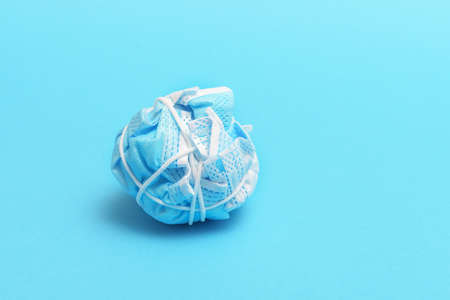 The concept of ending a pandemic. Crumpled medical mask on blue background.