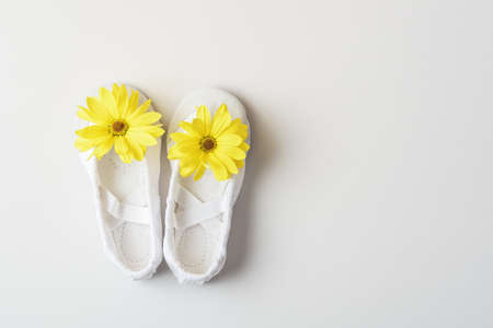 White ballet flats with yellow flowers on a white background with copy space. 版權商用圖片
