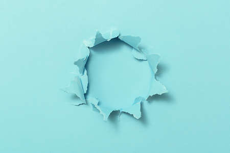 Torn hole in blue paper with copy space.