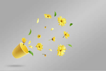 Yellow cup with flying yellow flowers on a gray background. The concept of spring.
