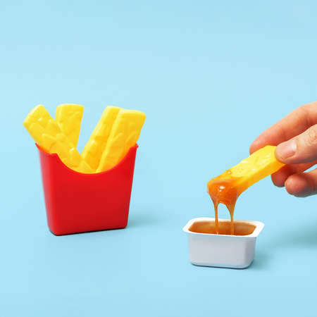 Creative concept of junk food. Fake fries are dipped in sauce.