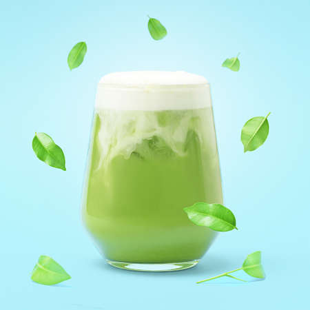 A glass of iced matcha latte on a blue background with falling leaves.