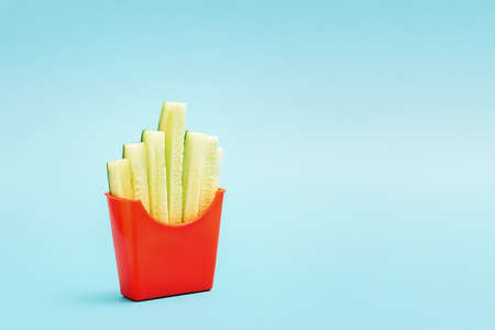 The concept of healthy eating. A cup of french fries with sliced cucumbers.