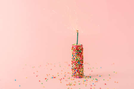 Creative concept of the holiday. Pink firecrackers with sweet balloons on a pink background.