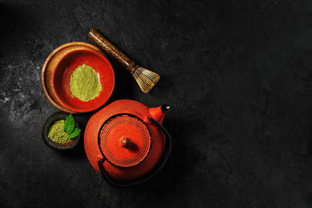 Matcha tea powder in a bowl with a kettle on a dark background. Top view. Stock Photo