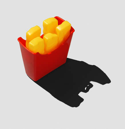 The concept of junk food. A box of fries and scary shade.