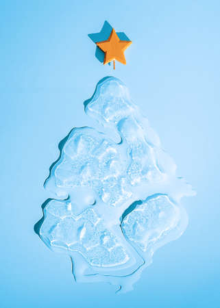 Christmas ice melting Christmas tree with a star on a blue background.