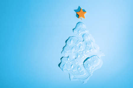 Christmas ice melting Christmas tree with star on blue background with copy space.