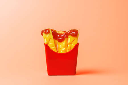 Plastic fries drizzled with fresh ketchup on an orange background.