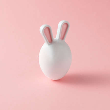 Easter egg with bunny ears on a pink background. A creative Easter concept.
