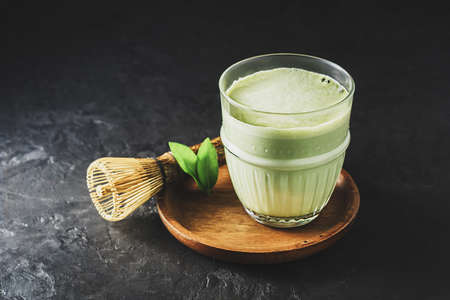 A glass of matcha tea on a dark concrete background with copy space. 免版税图像