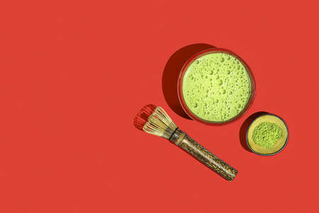 Freshly made matcha tea with ingredients on a red background. Top view.