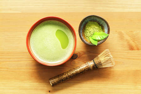 A bowl of matcha tea on a wooden table with a whisk and powder.