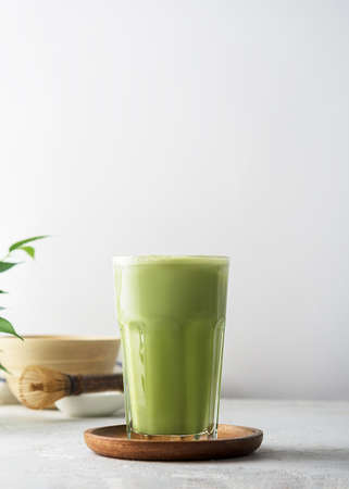 A glass of matcha tea on a concrete background with copy space.