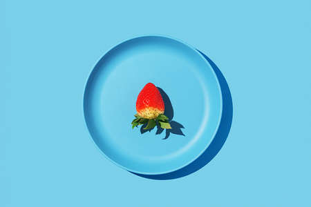 A single strawberry on a blue plate on a blue background. Top view.