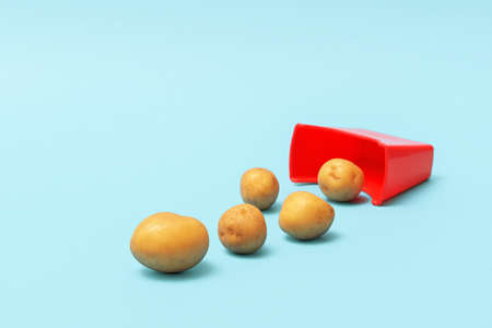 The minimalist concept of junk food. Scattered natural potatoes from a red cup on a blue background.