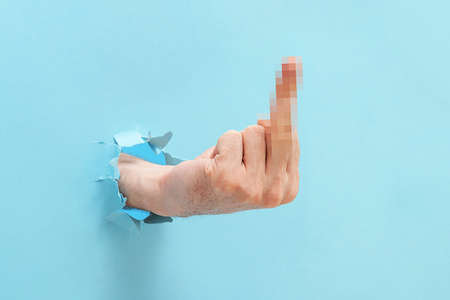 A man's hand shows a gesture of fuck you or fuck off through the torn blue paper.