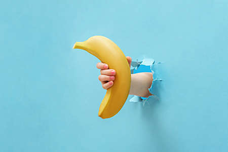 The girl's hand holds a banana through the torn blue paper. 免版税图像