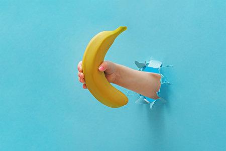 The girl's hand holds a banana through the torn blue paper. Reklamní fotografie