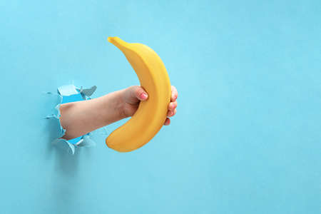 The girl's hand holds a banana through the torn blue paper. Stock Photo