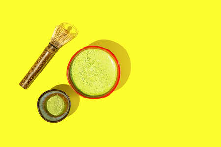 Freshly made matcha tea with ingredients on a yellow background. Top view.