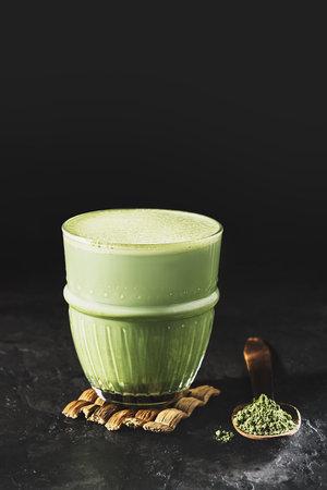 A glass of matcha tea on a dark concrete background with copy space. Reklamní fotografie