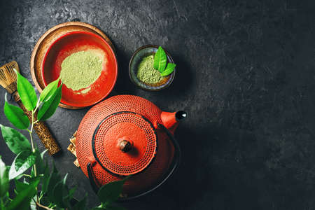 Powder matcha tea with kettle on a dark background with copy space. 免版税图像