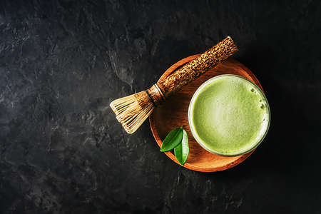 A glass of matcha latte tea on a dark concrete background with a copy space.