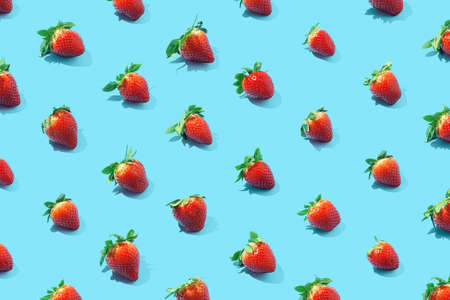 Seamless pattern of fresh strawberries on blue background. Top view.