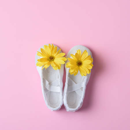 White ballet flats with yellow flowers on a pink background. Top view. 免版税图像