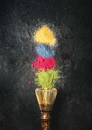 Various matcha tea powders with a whisk on a dark concrete background. Top view.