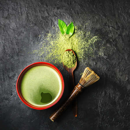 A bowl of matcha tea with scattered powder on a dark background. Top view. 免版税图像