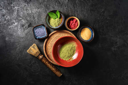 Various matcha tea powders on a dark concrete background. Top view.
