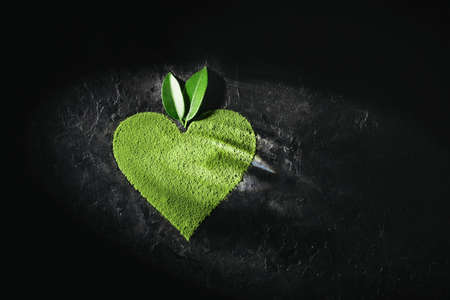 Powder matcha tea in the shape heart on a dark background with copy space. Reklamní fotografie