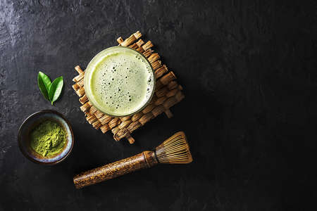 A glass of matcha tea with the ingredients on a dark concrete background with copy space.